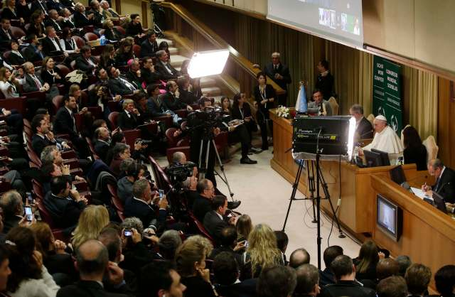 Pope Francis talks to a camera linked with Argentina as he leads a meeting for the 4th World Congress of Educational Scholas Occurrentes in the Synod hall at the Vatican